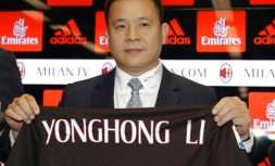 Chinese businessman Yonghong Li poses with an AC Milan jersey with his name during a press conference to illustrate takeover of AC Milan soccer club by a Chinese consortium, in Milan, Italy, Friday, April 14, 2017. A new era began at AC Milan on Thursday after the sale of Italy's most successful club to a Chinese-led consortium ended Silvio Berlusconi's 31 years in charge. (AP Photo/Antonio Calanni)