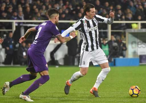 Fiorentina's Cristian Biraghi, left, and Juventus' Federico Bernardeschi go for the ball during a Serie A soccer match between Fiorentina and Juventus at the Artemio Franchi stadium in Florence, Italy, Friday, Feb. 9, 2018. (Maurizio Degl'Innocenti/ANSA via AP)