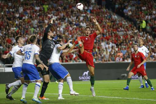 Portugal's Andre Silva, centre, challenges Italy goalkeeper Gianluigi Donnarumma and three Italian defenders during the UEFA Nations League soccer match between Portugal and Italy at the Luz stadium in Lisbon, Monday, Sept. 10, 2018. (AP Photo/Armando Franca)