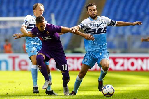Fiorentina's  Marko Pjaca, center, competes for the ball with Lazio's Marco Parolo, right, and Lazio's Lucas Leiva during a Serie A soccer match between Lazio and Fiorentina at Rome's Olympic stadium, Sunday Oct. 7 2018. (Angelo Carconi/ANSA via AP)
