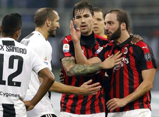 AC Milan's Gonzalo Higuain, right, talks with Juventus' Giorgio Chiellini, left, during a Serie A soccer match between AC Milan and Juventus, at Milan's San Siro stadium, Sunday, Nov. 11, 2018. (AP Photo/Luca Bruno)