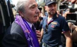Rocco Commisso wears a Fiorentina scarf as he arrives at the Florence airport, Italy, Thursday, June 6, 2019. Italian-American businessman Rocco Commisso has completed his takeover of Serie A soccer club Fiorentina. No financial details were disclosed but the deal is reportedly worth about 160 million euros. Commisso also owns the New York Cosmos of the North American Soccer League. (Claudio Giovannini/ANSA via AP)
