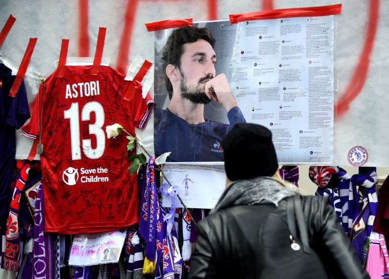 Football fans hang scarves and tributes to late Fiorentina football team captain Davide Astori on the fence of the team stadium on March 7, 2018 in Florence. Italian footballer Davide Astori likely died from a cardiac arrest linked to the slowing of his heart rate following the initial results of his autopsy. Fiorentina and Astori's former club Cagliari announced they will retire his number 13 shirt in honour of the 31-year-old Italy international, who was found dead in his hotel room on Sunday ahead of a Serie A match at Udinese. / AFP PHOTO / Filippo MONTEFORTE